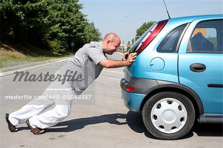 Man pushing a broken car or a car out of gas Stock Photo - Budget Royalty-Free, Image code: 400-05068357