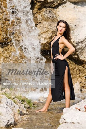 sensual brunette in fashion pose with black dress in front of a waterfall Stock Photo - Budget Royalty-Free, Image code: 400-05078491