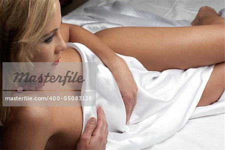 Sensual naked young blonde adult Caucasian woman, wrapped in a satin, silk sheet on a bed in her bedroom. High contrast lighting. Stock Photo - Budget Royalty-Free, Image code: 400-05083138