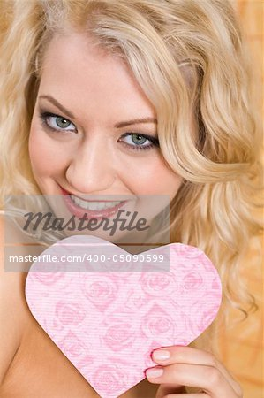 Portrait of glamorous girl holding pink paper heart in hand and smiling Stock Photo - Budget Royalty-Free, Image code: 400-05090599