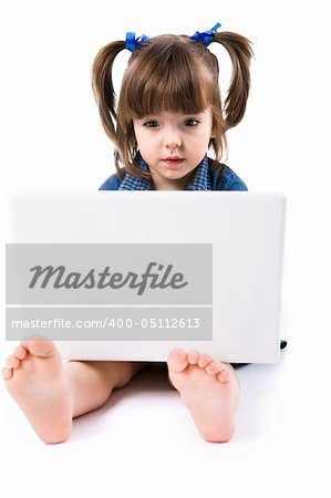 Image of cute preschooler sitting on floor in front of laptop and looking into its screen