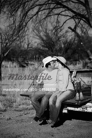 Man and woman in cowboy hats kissing on back of pickup truck Stock Photo - Budget Royalty-Free, Image code: 400-05125130