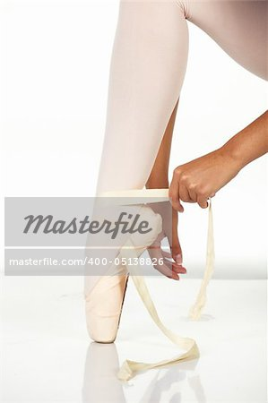 Young female ballet dancer showing how to tie a ballet Pointe Shoe against a white background. NOT ISOLATED Stock Photo - Budget Royalty-Free, Image code: 400-05138826