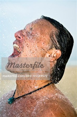 A handsome forties man is taking a wash under a powerful shower at the beach. Stock Photo - Budget Royalty-Free, Image code: 400-05149577