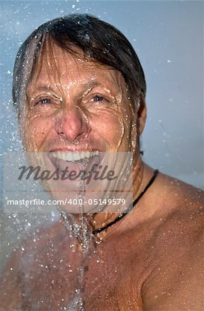 handsome forties man is laughing as he has fun under a powerful shower. Stock Photo - Budget Royalty-Free, Image code: 400-05149579