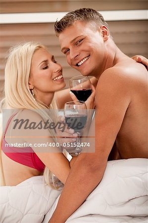 Couple sharing wine in bed Stock Photo - Budget Royalty-Free, Image code: 400-05152474