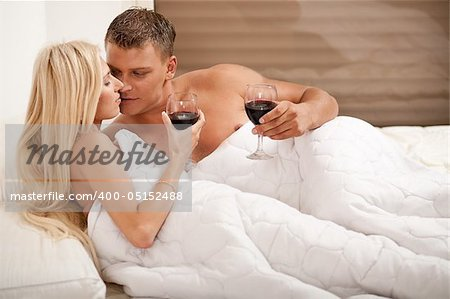 Couple drinking on the bed in bedroom Stock Photo - Budget Royalty-Free, Image code: 400-05152488