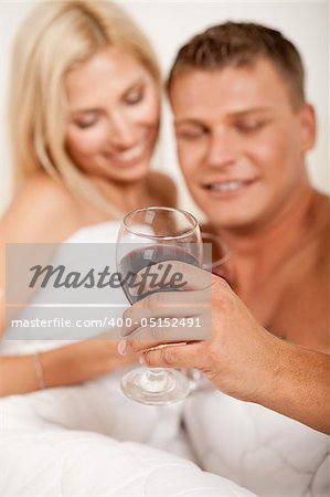 Young couple toasting champagne in bed Stock Photo - Budget Royalty-Free, Image code: 400-05152491