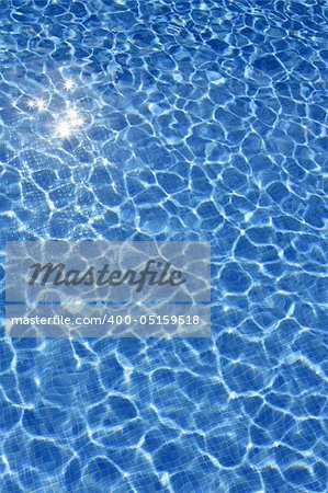 Blue water texture, tiles pool in sunny day with light reflections