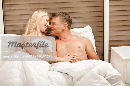 Caucasian couple embracing and enjioying in bed Stock Photo - Budget Royalty-Free, Image code: 400-05174671