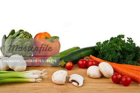 Image of a wood cutting board with assorted vegetables on a white background Stock Photo - Budget Royalty-Free, Image code: 400-05199876