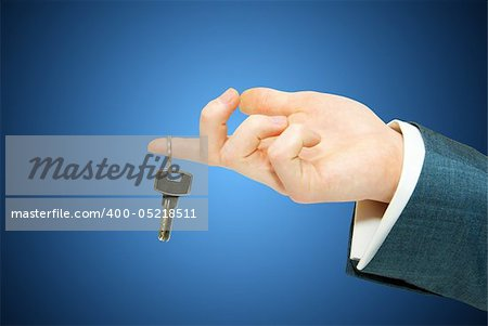 hand holds a key isolated on blue