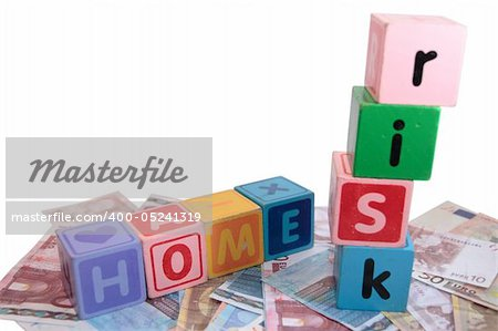 assorted childrens toy letter building blocks against a white background on money that spell home risk Stock Photo - Budget Royalty-Free, Image code: 400-05241319