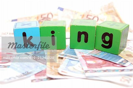 assorted childrens toy letter building blocks against a white background on money that spell king Stock Photo - Budget Royalty-Free, Image code: 400-05241320