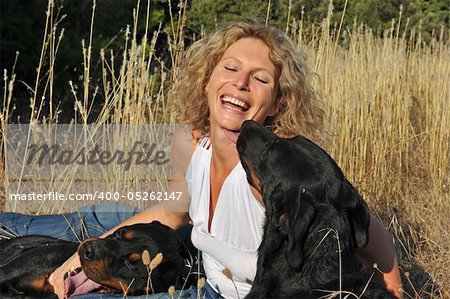 laughing young woman and her two dogs: rottweiler and french shepherd Stock Photo - Budget Royalty-Free, Image code: 400-05262147