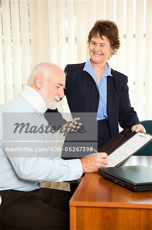 Personal injury lawyer winks as she signs a gullible client. Stock Photo - Budget Royalty-Free, Image code: 400-05267398