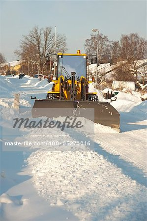 A tractor shoveling snow in a suburban street Stock Photo - Budget Royalty-Free, Image code: 400-05270016