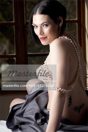 Sexy naked young caucasian adult woman with red lips, short black hair and a pierced eyebrow, covered in a dark satin sheet and sitting on a bed and wearing a string of pearls Stock Photo - Budget Royalty-Free, Image code: 400-05276286