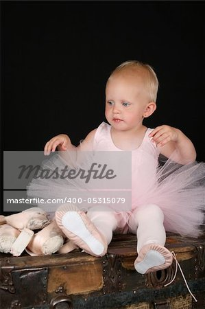 Beautiful blond baby wearing a ballet costume sitting ontop of antique trunk Stock Photo - Budget Royalty-Free, Image code: 400-05315079