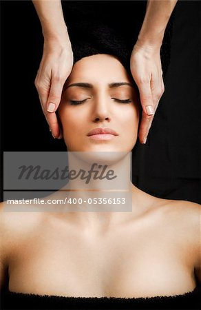 beautiful young female receiving gentle facial massage, eyes
