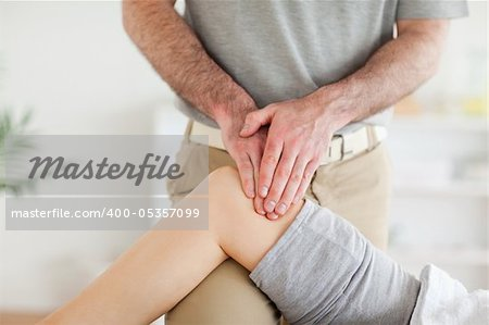 Chiropractor massaging a charming woman's knee in a room