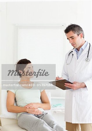 Woman lying down talking to a doctor in an office