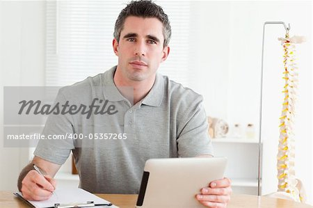 Male Doctor working with a tablet and a chart in a room