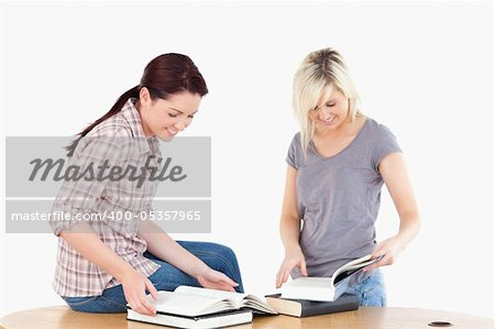 Two gorgeous female students learning at table