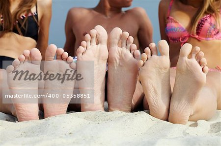 Soles of teenagers sunbathing on sandy beach Stock Photo - Budget Royalty-Free, Image code: 400-05358851