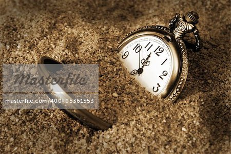 A pocket watch is buried in the dirty sand. Stock Photo - Budget Royalty-Free, Image code: 400-05361553