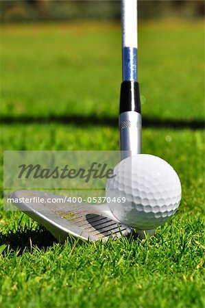 Golf ball and driver, ready to strike, on a real golf course.