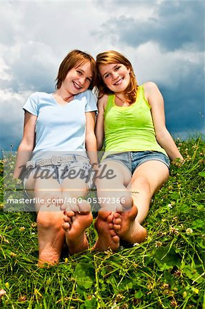 Two young teenage girl friends sitting barefoot on summer meadow Stock Photo - Budget Royalty-Free, Image code: 400-05372366