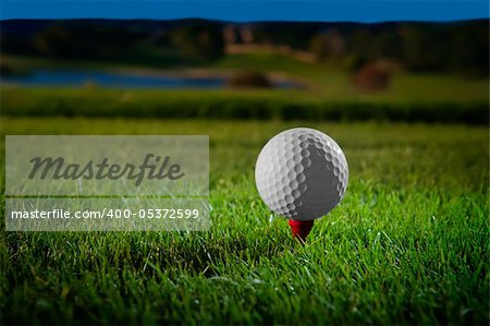 Image of a beautifully lit golf ball on a red tee with course in background Stock Photo - Budget Royalty-Free, Image code: 400-05372599