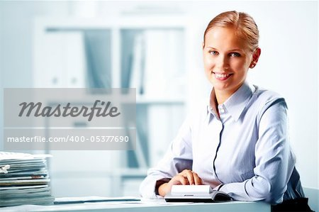 Portrait of a young happy businesswoman looking at camera in office