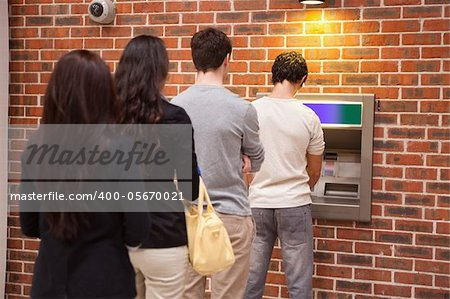 Young people queuing to withdraw cash in an ATM