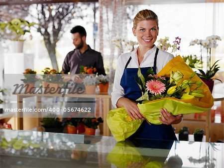 Female sales assistant working as florist and holding bouquet with customer in background. Horizontal shape, waist up