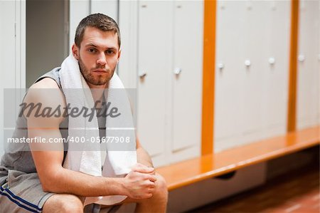 Handsome sports student sitting on a bench with a towel