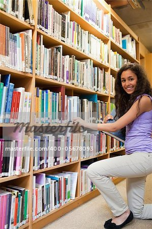Portrait of a smiling female student choosing a book in a library Stock Photo - Budget Royalty-Free, Image code: 400-05678093