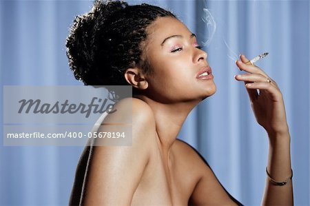 Beautiful sensual and naked woman enjoying a cigarette on blue baggrund Stock Photo - Budget Royalty-Free, Image code: 400-05678194