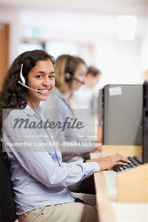 Portrait of a smiling assistant working with a computer in a call center