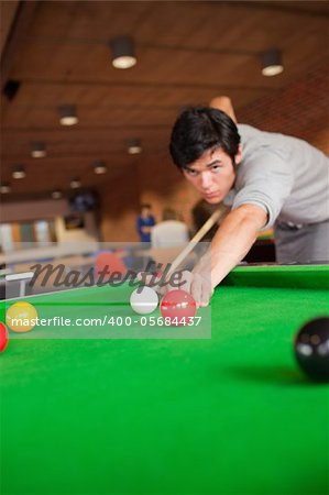 Portrait of a student playing pool in a student home