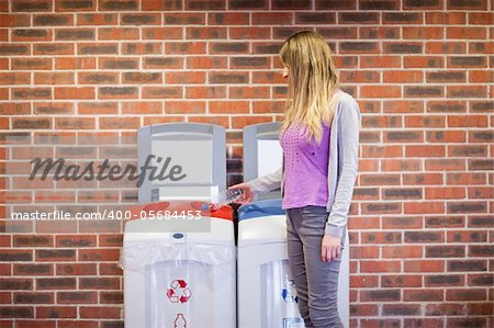 Cute woman recycling a plastic bottle