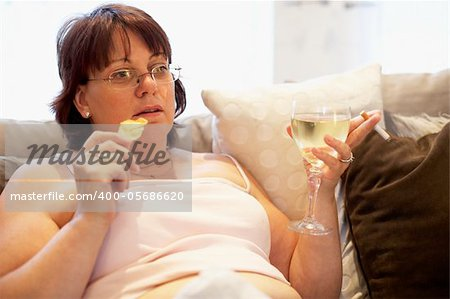 Overweight Woman Relaxing On Sofa Stock Photo - Budget Royalty-Free, Image code: 400-05686620
