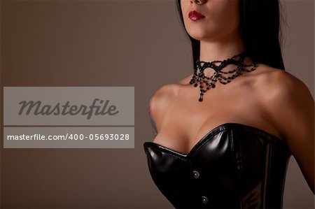 Close-up shot of busty woman in black corset, studio shot on creamy background Stock Photo - Budget Royalty-Free, Image code: 400-05693028