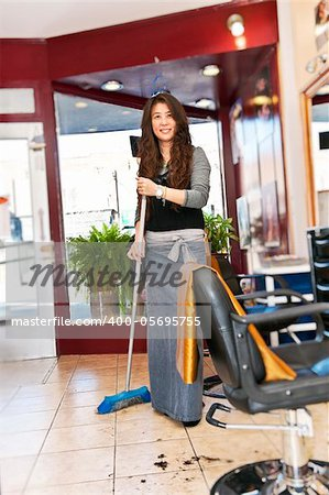 Smiling hairstylist sweeping hair clippings on floor in her salon Stock Photo - Budget Royalty-Free, Image code: 400-05695755