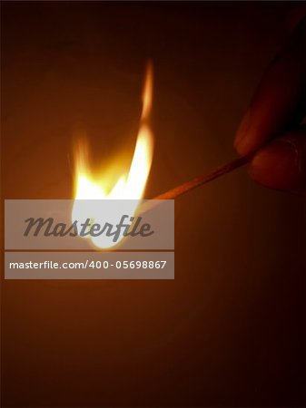 hand holding a blazing match lighting just as it burst into flame Stock Photo - Budget Royalty-Free, Image code: 400-05698867