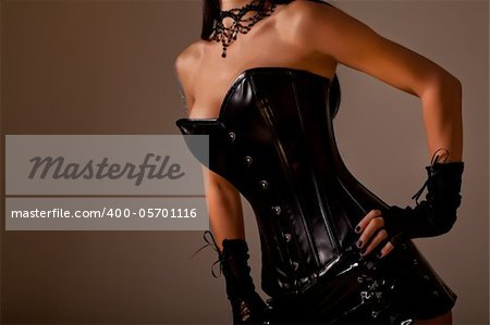 Close-up shot of busty woman in black leather corset, studio shot on golden background Stock Photo - Budget Royalty-Free, Image code: 400-05701116