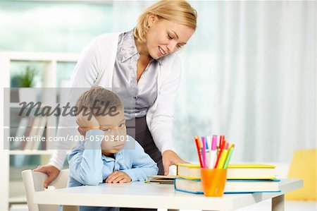 Portrait of tired boy looking at camera while tutor explaining something near by Stock Photo - Royalty-Free, Artist: pressmaster, Code: 400-05703401