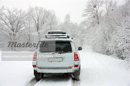 Snowy winter road behind an unrecognizable car Stock Photo - Budget Royalty-Free, Image code: 400-05704849