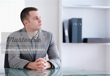 Businessman sitting behind a table and thinking